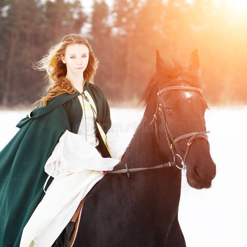 Young girl in white dress and cape riding horse royalty free stock photo