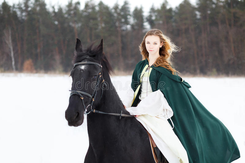 Young girl in white dress and cape riding horse. Young girl in white dress and green cape riding horse on snowy field near forest royalty free stock photo