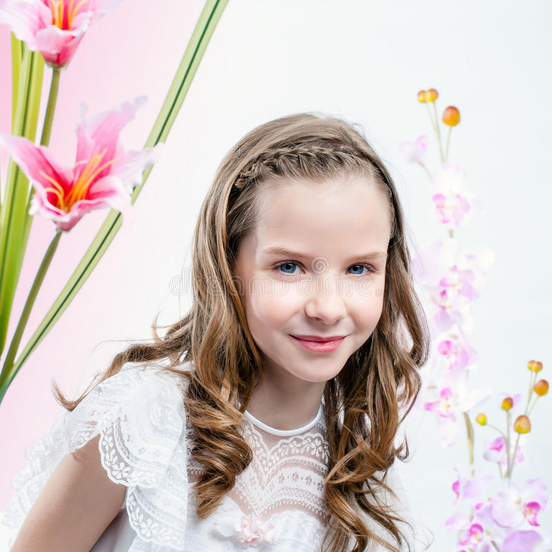Young girl in white dress among flowers. royalty free stock photos