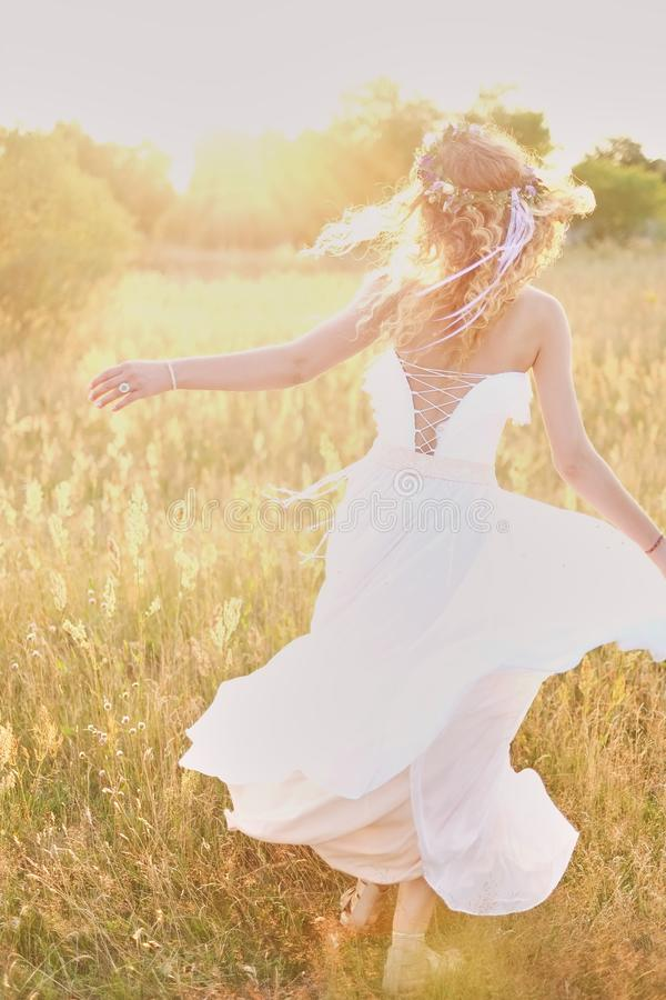 Young girl in a white dress in the meadow. Woman in a beautiful long dress posing in the garden. Stunning bride in a wedding dress royalty free stock photos