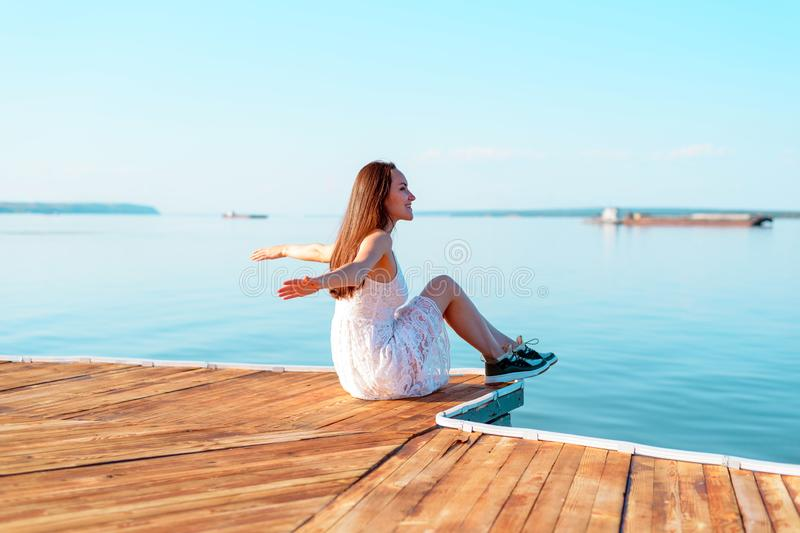 Young girl in white dress sitting on a wooden pier with open hands looking into the distance of the sea, freedom, clean air, dream stock image