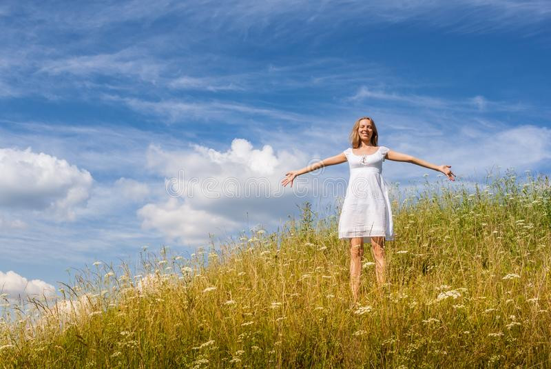 Young girl in white dress is standing on grass hill on blue sky background in summer day. royalty free stock image