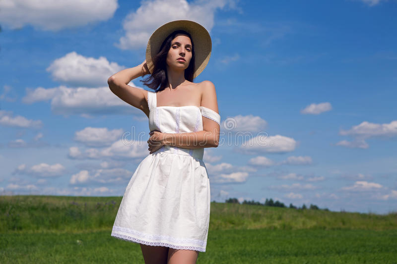 Young girl in white dress and straw hat stock photo