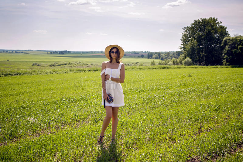 Young girl in white dress and straw hat stock image