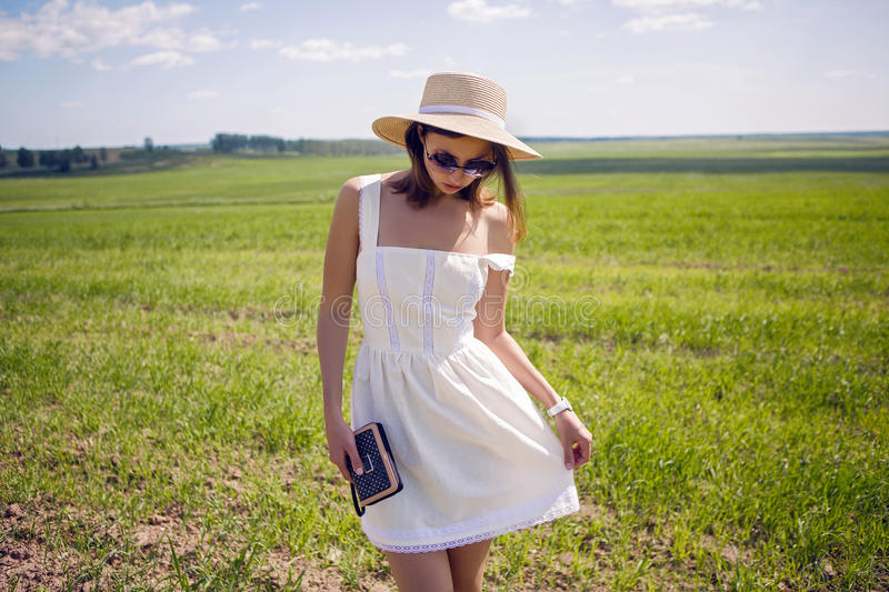 Young girl in white dress and straw hat stock photography