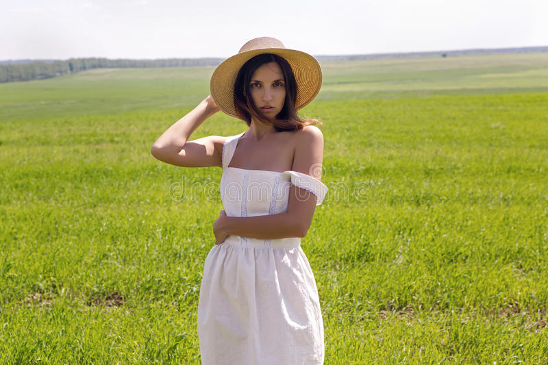 Young girl in white dress and straw hat stock images