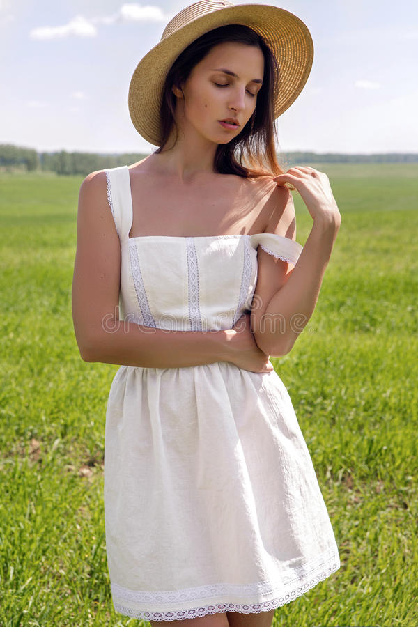 Young girl in white dress and straw hat royalty free stock image