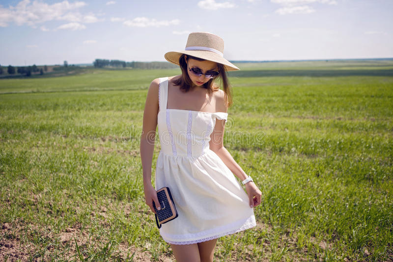 Young girl in white dress and straw hat royalty free stock photos
