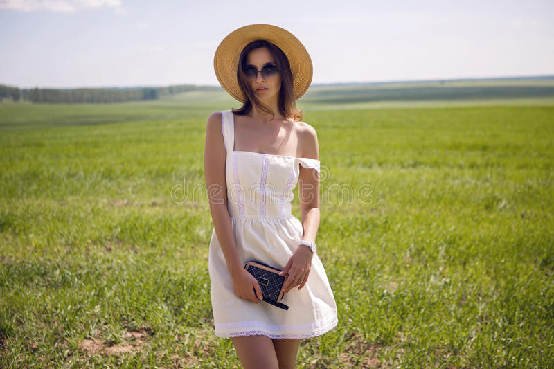 Young girl in white dress and straw hat royalty free stock photography