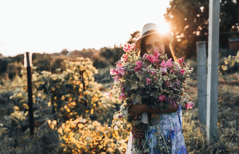 Young girl in white hat and dress covered her face with a large bouquet of beautiful pink flowers, sunset on the stock photos