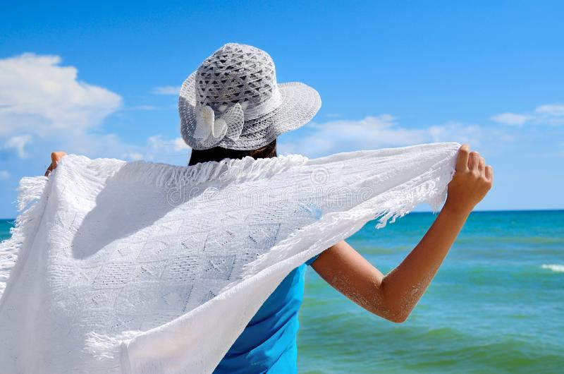 Young girl in a white hat on the sea beach. Clean, sandy beach against the blue sea stock images