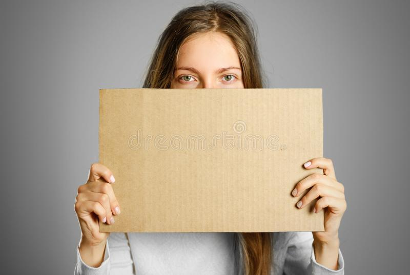 A young girl in a white jacket holding a piece of cardboard. Prepared for your text royalty free stock image