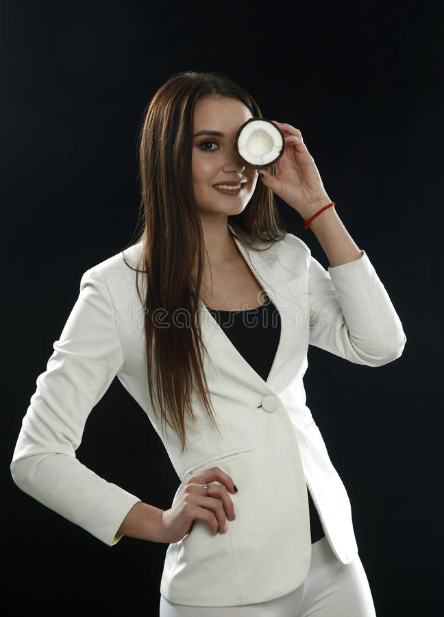 Young girl in a white jacket holds a coconut near her eye and smiles on a black background royalty free stock image