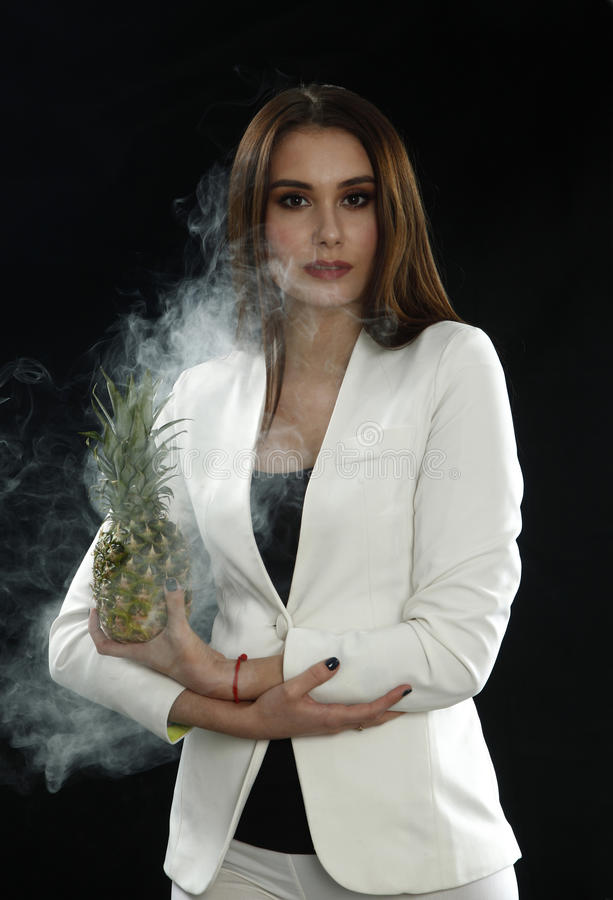 A young girl in a white jacket holds a pineapple in her hands and smiles on a black background, covered with smoke vapor royalty free stock photo