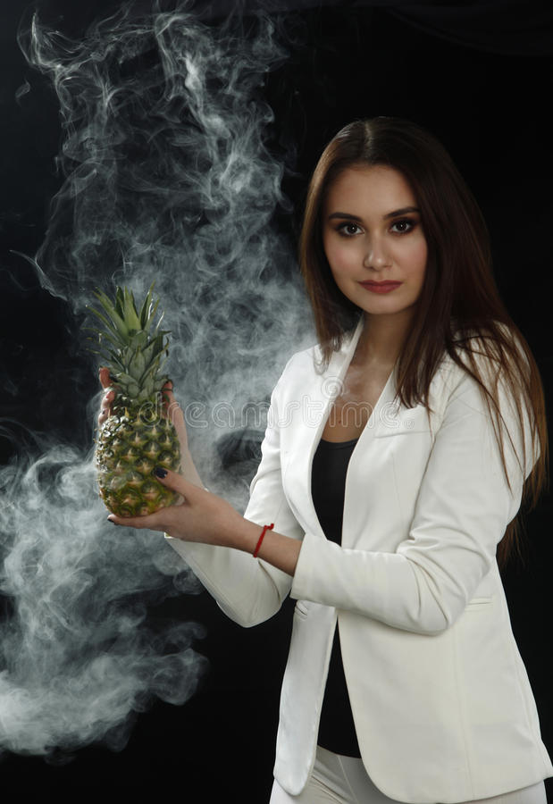 A young girl in a white jacket holds a pineapple in her hands and smiles on a black background, covered with smoke vapor stock photo