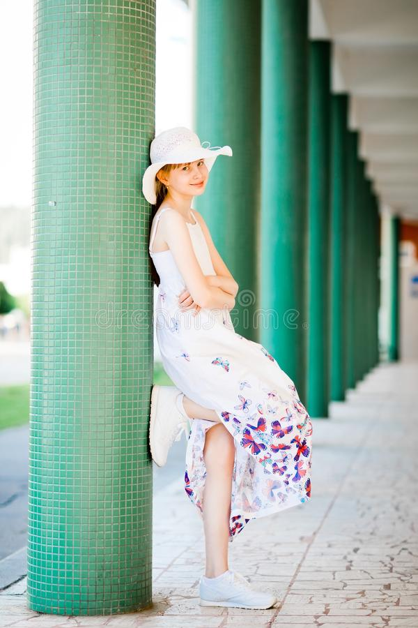 Young girl in white long dress posing at colonnade stock photo