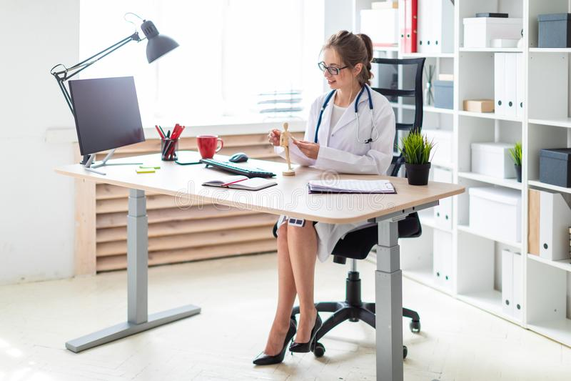 A young girl in a white robe sits at a computer desk and holds a wooden human figure in her hand. A beautiful young girl with glasses and a white coat is stock photos