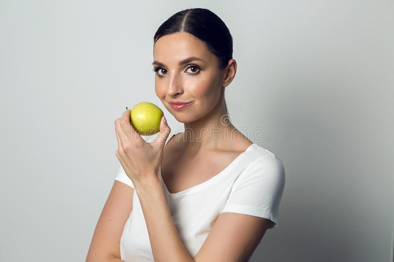 Young girl in a white t-shirt with an apple royalty free stock image