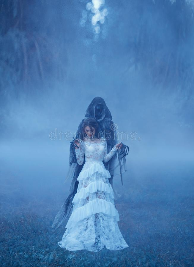 Young girl in a white vintage dress and a silver necklace is standing on frozen grass in a thick blue mist in Death. Captivity and looking down. creative chill stock images
