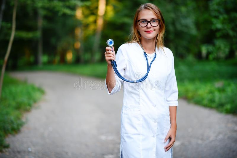 a young girl who is a doctor stands outside, holds the stethoscope in the right hand royalty free stock photo