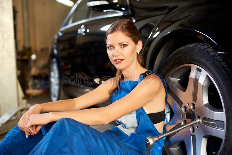 Young girl works as a mechanic in a car service royalty free stock photo