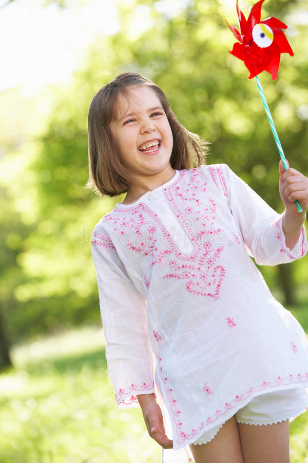 Download Young Girl With Windmill In Field Stock Image - Image: 26106171