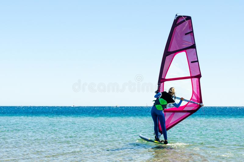 Young girl windsurfer beginner learns to ride in the sea in Egypt Dahab South Sinai royalty free stock image