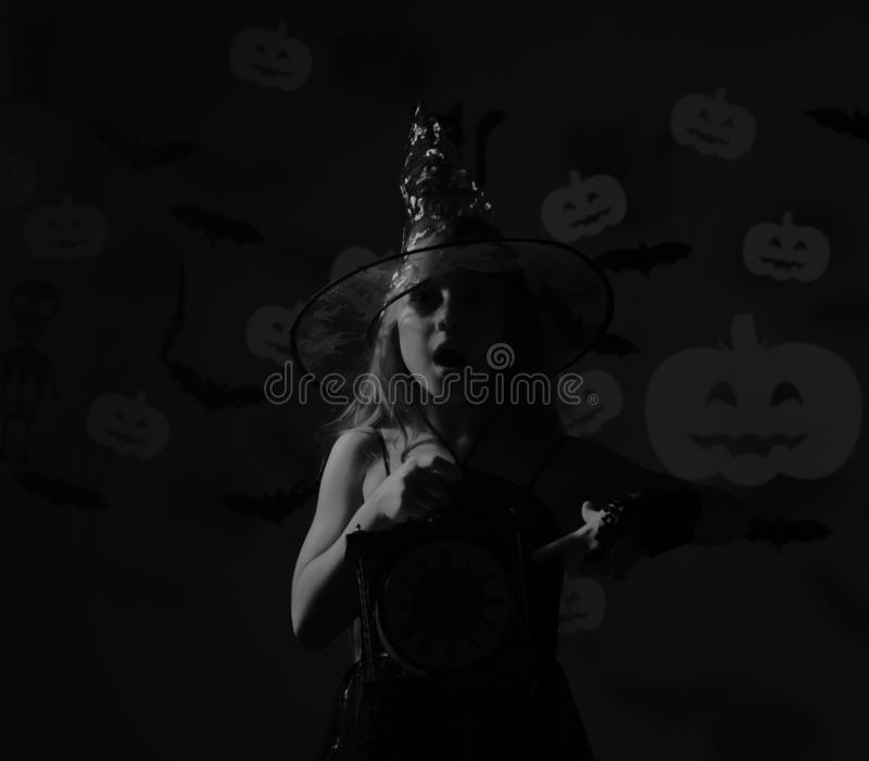 Young girl in witch halloween costume with big old clock royalty free stock photography