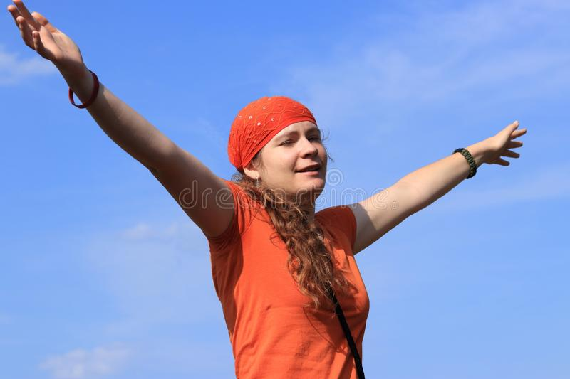 Young girl woman with long wavy brown hair, orange T-shirt tee-shirt and bandanna scarf is happy in summer sunny day and sky royalty free stock images