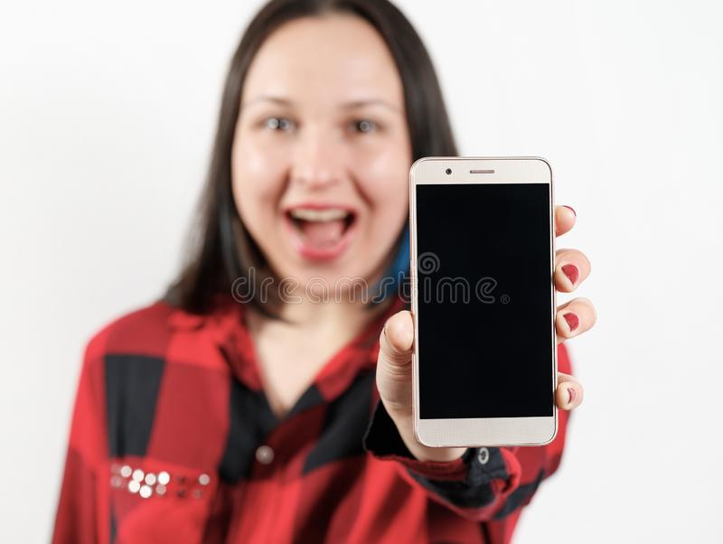 A young girl woman in a red and black shirt is holding a smartphone with a blank black screen vertically in front of her. A young girl woman in a red-black shirt royalty free stock photos