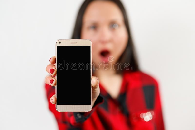 A young girl woman in a red and black shirt is holding a smartphone with a blank black screen vertically in front of her. A young girl woman in a red-black shirt stock images
