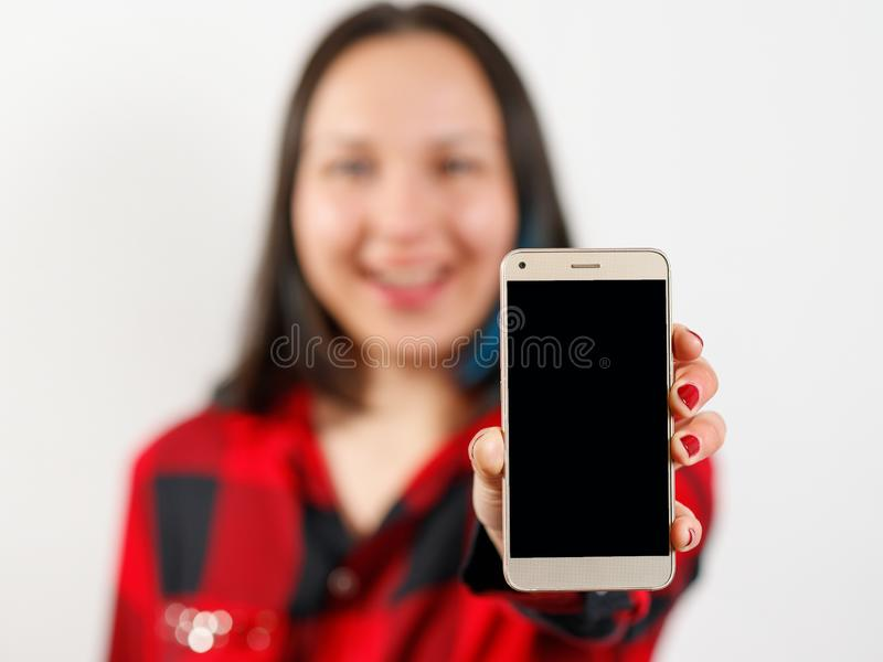 A young girl woman in a red and black shirt is holding a smartphone with a blank black screen vertically in front of her. A young girl woman in a red-black shirt stock photography