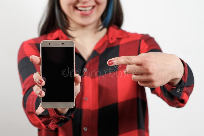 A young girl woman in a red and black shirt is holding a smartphone with a blank black screen vertically in front of her. A young girl woman in a red-black shirt stock photo