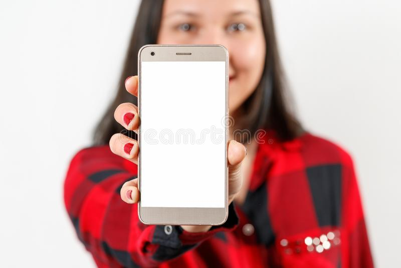 A young girl woman in a red and black shirt is holding a smartphone with a blank white screen vertically in front of her. A young girl woman in a red-black shirt royalty free stock photography