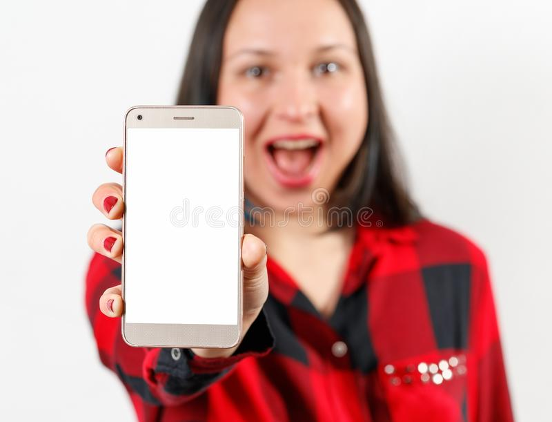 A young girl woman in a red and black shirt is holding a smartphone with a blank white screen vertically in front of her. A young girl woman in a red-black shirt stock photo