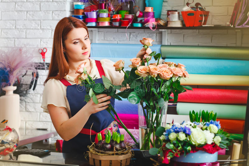 Young girl working in a flower shop, Florist woman makes a bouquet royalty free stock image