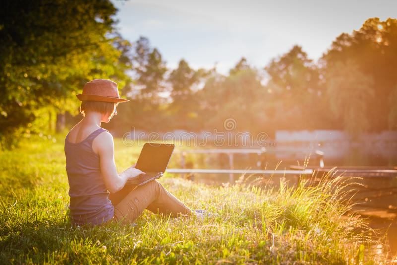Young girl working/studing in the park royalty free stock images