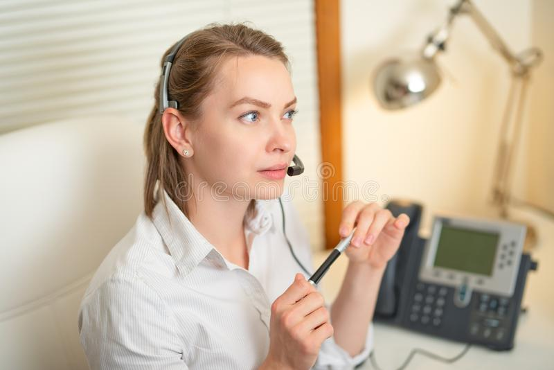 A young girl works in a call center. for a working place. . earphone and microphone. Support service. Help desk. Horizontal photo.  stock images
