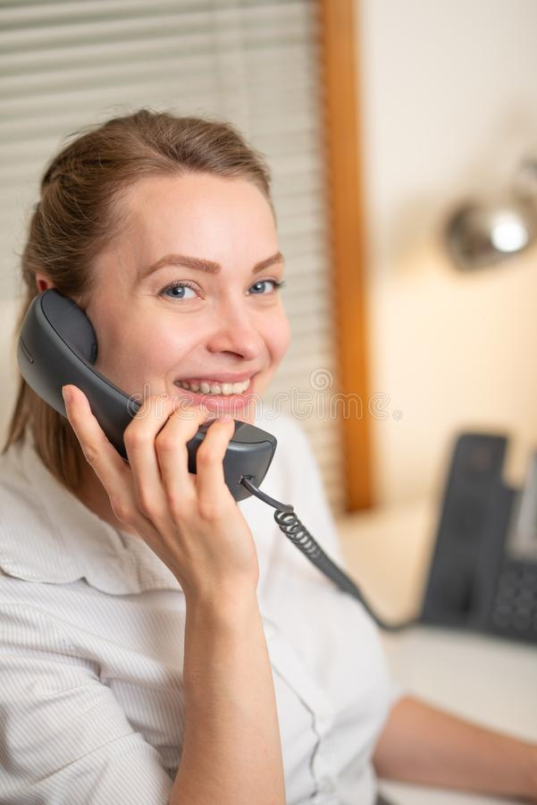 A young girl works in a call center. for a working place. . earphone and microphone. Support service. Help desk. Horizontal photo.  royalty free stock photography