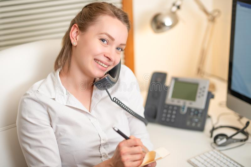 A young girl works in a call center. For a workplace with a telephone. A microphone with a microphone. Support service. Help desk stock photography