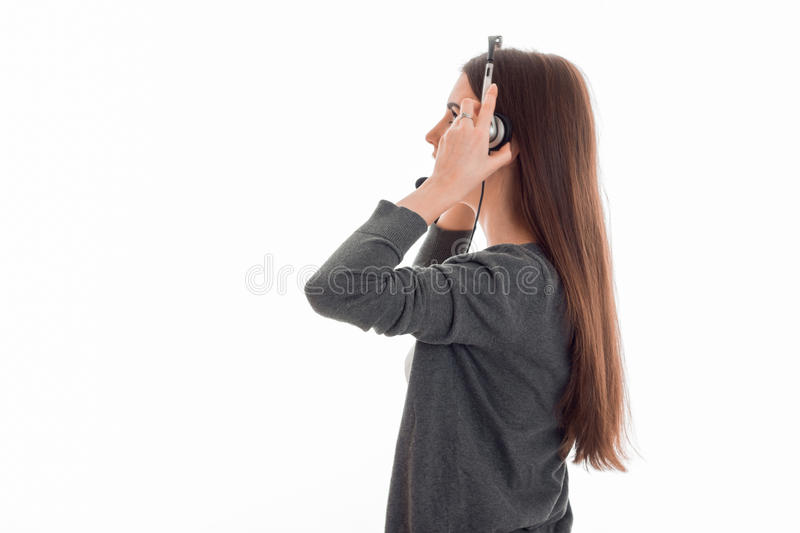 A young girl is worth turning sideways to the camera and listening to headphones royalty free stock image