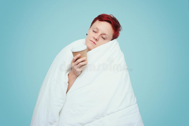 Young girl wrapped in white thick blanket and hold paper glass of hot drink. Holiday, day of rest. Sick person. Caught a cold. stock photography