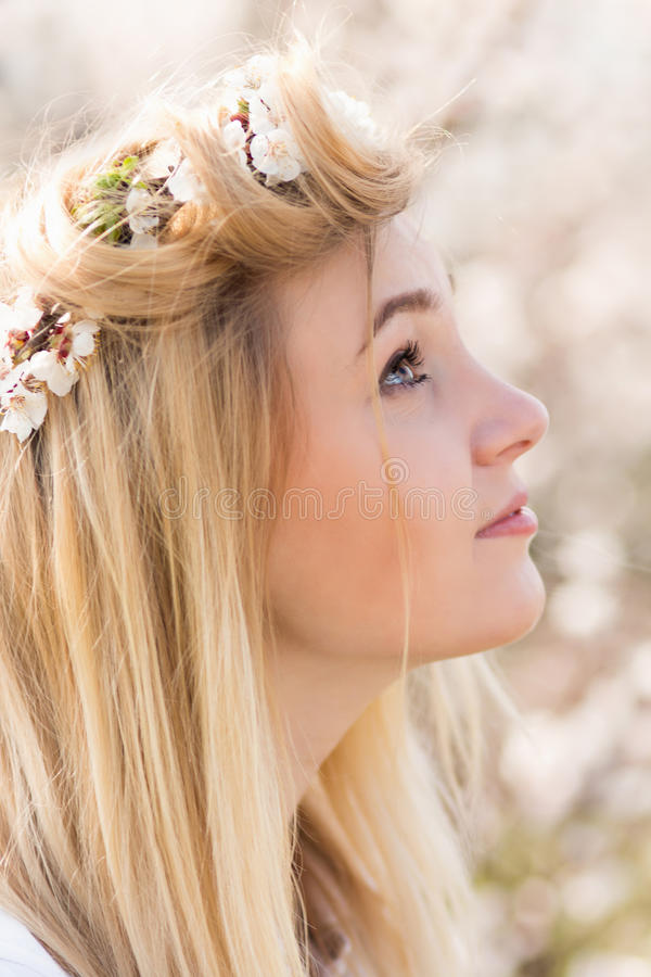 Young girl in a wreath of flowers with apricot royalty free stock image