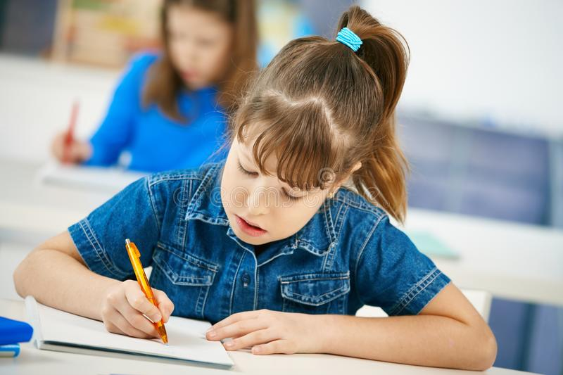 Young girl writing at school. Sitting in class with other girl in background stock photos
