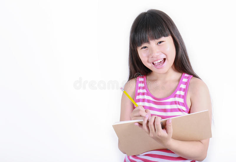 Young girl writing something with yellow pencil. Isolated on white, back to school concept stock photography