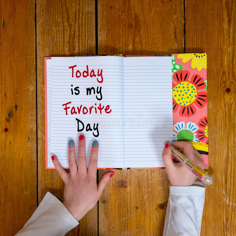 Young girl writing the words Today is my Favorite day in a vintage diary royalty free stock photos