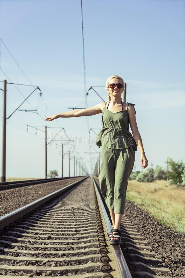 A young girl of 17 years old blonde with pigtails posing on a railroad bed stock images