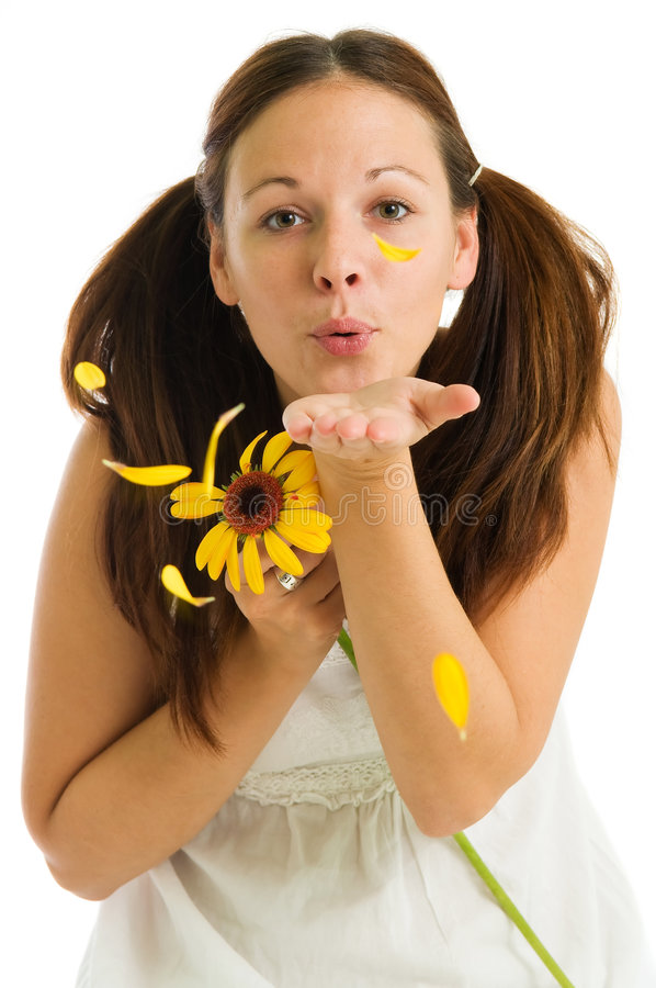Young girl and yellow flower. Young attractive girl blowing into petals of yellow flower on the white background stock photography