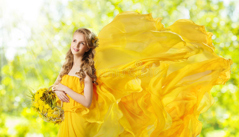 Young Girl with Yellow Flowers Dandelion Basket, Fashion Model royalty free stock photo