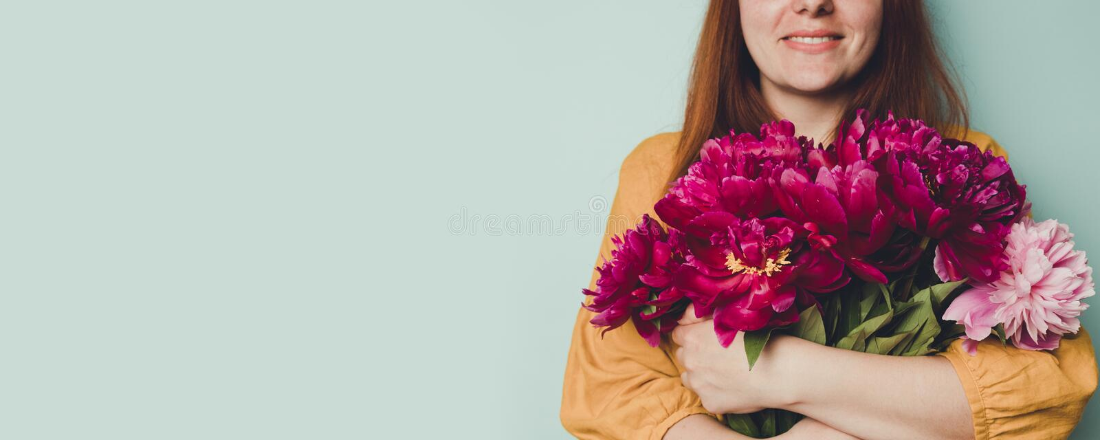 Female hand holding beautiful bouquet with fragrant peonies on light blue background stock image